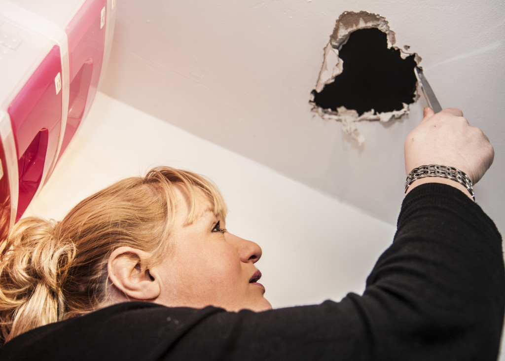 Tanya Williams with the hole in the ceiling of her lingerie shop where she rescued a cat which got stuck in her roof. See SWNS story SWPEEP; A cat whose curiosity got the better of it was cut free from the roof of a lingerie shop after the owner heard mysterious wails coming from the ceiling. Cedric the tabby cat became trapped in the roof of Provocative Pleasures in Swindon last week. Shop owner Tanya Williams sprung to action armed with a pair of scissors and cut through the plaster of the ceiling to rescue the peeping tom. The mystery meowing had plagued Tanya for days before she finally realised the feline noises came from above.